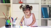 berçário : Diligent girl developing her creativity drawing in crayons