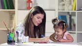 Young woman babysitting little girl drawing together with her