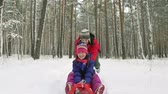 irmã : Happy siblings sledding through the snow