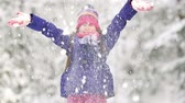 snowfall : Lovely little girl throwing a handful of snow up in the air