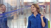 shoppingbag : Joyful girl with purchases passing shopping windows Stock Footage
