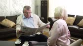 diário : Senior husband reading the daily newspaper to his wife