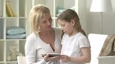 noivo : Mother and daughter sharing affectionate conversation and using portable gadget