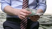 bem estar : Unrecognizable man counting dollars Stock Footage