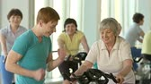 tonus : Young instructor motivating senior woman to cycle faster