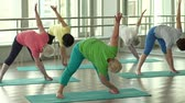 posture : Women following coach's instructions and doing utthita trikonasana Stock Footage