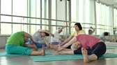 assentado : Five women performing hamstring stretching to the right