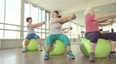 грудь :  Dolly shooting of senior women exercising on fitball with weighted ball
