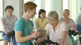 instrutor : Focus on instructor with tablet and woman on exercise bicycle