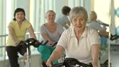 tonus : Focus on elderly woman cycling in gym