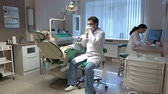 диагностика : Interior of dentist's office, doctor consulting patient and assistant at computer