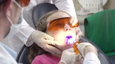 restauração : Full face of preteen patient at the recliner chair having her tooth cured with light by unrecognizable practitioner and assistant Vídeos