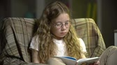 habilidade : Static shot of girl wearing goggles reading a book Vídeos