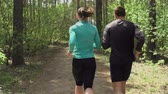 стройный : Tracking shot from behind of boy and girl running in slow motion