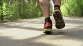 holandês : Dutch angle of male hairy legs running in park in slow-mo, tracking shot from behind