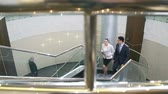 spacious : High angle of young colleagues climbing stairs and talking, elderly man in the background talking on the phone Stock Footage