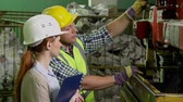 inclinar : Close up of male worker and female inspector examining work of machine tool