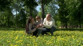 подарок : Family of three in the field, father presenting wildflower to little daughter