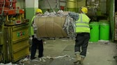 processo : Two male laborers in helmets loading paper waste on hoisting crane for further process
