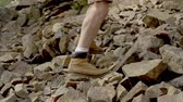 scrambling : Slow motion of male athletic legs clambering up the rocky hill Stock Footage