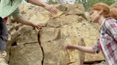scrambling : Backpackers climbing the cliff with the help of their friend