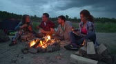 assentado : Pan of four people seated on ground eating by campfire and chatting Stock Footage