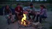 quatro : Four young friends chilling by fire telling funny stories