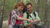 dráha : Handheld close up of girl and boy discussing the route on the map