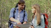 excursão : Tilt up of hiking couple deciding on direction of their further trip with the help of map