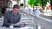 formalwear : Businessman surfing the net on touchpad in outdoor café, unrecognizable people passing by Stock Footage