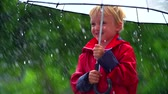 guarda chuva : Close up of little boy crinkling under umbrella in the rain and wind