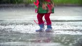 guarda chuva : Tilt up of little girl bouncing and splashing happily in the rain