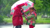 escondido : Girl letting boy under her umbrella Stock Footage