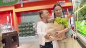 mercado : Slow motion of two little girls carrying a paperbag stuffed with produce, approaching camera