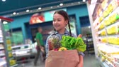 mercado : Handheld camera shot of happy girl with shopping bag going along supermarket shelves in slow motion Vídeos