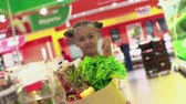 mercado : Little girl approaching camera in slow motion and looking straight at camera, holding a heavy paperbag with foodstuff