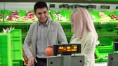 massa : Couple at self-service supermarket weighing grapefruit at weight scale