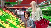 supermarket : Mother selecting fruits with her two kids Stock Footage