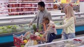 mercado : Family of three going to cash till, daughter riding the full shopping cart