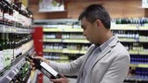 supermarket : Handsome guy of mixed race choosing wine in the supermarket Stock Footage