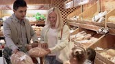 этикетка : Family of four selecting bread and putting it in shopping cart which is already full
