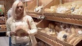 этикетка : Blond lady picking bread from shelf, smelling it and leaving, man hesitating with choice a bit longer