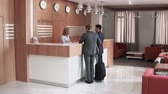residência : Hotel lobby cozy interior, guests going through check-in procedure, producing documents Stock Footage