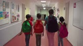 passagem : Camera following four kids with schoolbags going along the school corridor and joyously chatting in slow motion Vídeos
