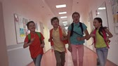 grade : Four blissful pupils running through school corridor, approaching camera in slow motion