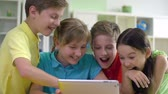 information : Four kids entertaining themselves using digital tab and laughing Stock Footage