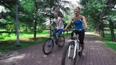 способ : Happy guys riding bikes and talking on their way