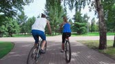 comum : Camera following two cyclists racing through the city park