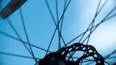 cog : Extreme close up of bicycle wheel spinning, through which blue sky is seen