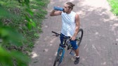 sedento : High angle of cyclist drinking from sipping bottle in slow motion Vídeos